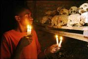 Apollan Odetta, a survivor of the 1994 Rwandan genocide, lights candles at a mass grave in Nyamata, Rwanda. Rwanda today is observing the 10th anniversary of the genocide that began April 7, 1994. Some 500,000 people died in the 100-day killing spree.