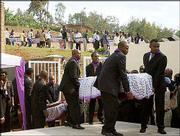 Survivors of the 1994 genocide in Rwanda carry coffins of the victims at dawn burial ceremony outside the capital, Kigali. The remains of victims recovered from mass graves and pit-latrines were buried during official ceremonies to mark the 10th anniversary of the government-orchestrated slaughter that took the lives of half a million people.