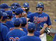 Kansas University's Matt Tribble, right, accepts congratulations after scoring against Wichita State. KU defeated the Shockers, 13-6, Wednesday night at Hoglund Ballpark.