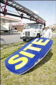 David Pryor, of Star Signs & Graphics Inc. of Lawrence, pulls down part of the Site Mini-Mart station's sign Monday.