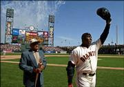 San Francisco's Barry Bonds, right, waves to the crowd after he hit a three-run home run to tie Willie Mays, left, at 660 for third on baseball's career list. Mays is holding a torch he presented to Bonds after the home run Monday in San Francisco.