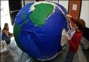 "Marissa Martin, 13, left, and Davis Ricker, 13, paint a 5-1/2-foot-diameter ""Earth ball"" at the Prairie Park Nature Center, 2730 Harper St. The ball was painted Tuesday for this weekend&squot;s Earth Day parade, and will also be featured when the center has its own Earth Day celebration on April 24"