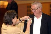 Former Kansas University track standout Wes Santee receives his 50-year pin from Leah Hemenway, the wife of Chancellor Robert Hemenway, at the Kansas Union. Members of the Class of '54 gathered for their 50-year reunion this weekend.
