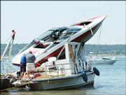 A motorboat lands on top of a houseboat in a wreck at Perry Lake. A passenger in the houseboat died in the Aug. 8, 2003, collision. Several lawsuits regarding the accident have been filed.