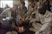 From left are Marine Cpl. Juan Perez, 25, Bronx, N.Y.; Pfc. Phillip Marquez, 21, of Coachella, Calif.; Cpl. Christopher Ebert, 21, of Forest City, N.C., and Staff Sgt. Damien Castilla, 38, from San Diego. The troops lit candles at the start of a Sunday church service in the living room of the home where they and Marines of Fox Company, 2nd Battalion, 1st Marine Regiment, have been staying for more than a week in northwest Fallujah, Iraq.