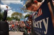 Jessica Militare, 13, of Miami, right, looks down toward a campaign sign as Democratic presidential candidate Sen. John Kerry, left, addresses the crowd during a campaign stop at the University of Miami.