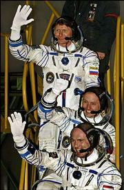 The crew of Russian Soyuz TMA-4 spacecraft waves before its launch at the cosmodrome Baikonur in Kazakhstan. Early today, crew members Russian cosmonaut Gennady Padalka, top, American NASA astronaut Michael Fincke, center, and Dutch ESA astronaut Andre Kuipers, bottom, headed to the international space station.