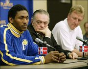 Indiana forward Ron Artest, left, listens to a question during a news conference as Pacers CEO Donnie Walsh, center, and Larry Bird look on. Artest spoke Monday in Indianapolis about being suspended for Game 2 against Boston and being chosen the NBA's Defensive Player of the Year.