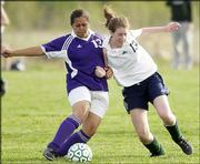 Seabury Academy's Elise Stella, right, battles Kansas City Harmon's Yesenia Salas for the ball. The Seahawks lost, 2-0, Monday at the Youth Sports Inc. fields.