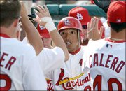 St. Louis outfielder So Taguchi high-fives teammates after scoring a run in a March 29 spring training game. In his third year with the Cards, Taguchi has become a dependable backup.