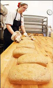 Baker Bri Hickman, Lawrence, transfers low-carbohydrate bread to the cooling racks at Great Harvest Bread Co., 807 Vt. The Atkins diet craze has affected many businesses like Great Harvest, which sells high-carb items such as breads and cookies. Subsequently, the bakery has introduced a bread with most of the wheat flour taken out, which reduces the amount of carbs.