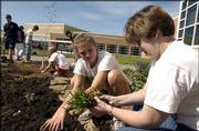 Southwest Junior High School students get an early start to Earth Day celebrations by planting vegetation in front of the school. Although the international observation of Earth Day is today, Southwest students, including Katelyn Hobbs, 15, above center, were marking the annual event Wednesday. Hobbs is shown with fellow students and Southwest Spanish teacher Danira Flores, at right.