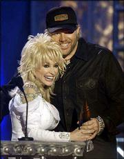 "Toby Keith gets a hug from host Dolly Parton as Keith is awarded the video of the year at the Flame Worthy Awards show in Nashville, Tenn. The Flame Worthy Awards are given to country music videos. Keith won Wednesday for his video ""American Soldier,"" and took home two other awards."