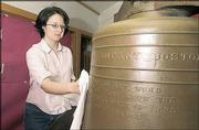Lawrence High School senior Karen Bently cleans a historic bell as part of a project to refurbish and display the artifact this fall at LHS to commemorate Lawrence's 150th birthday. The bell weighs 1,600 pounds.