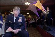 Air Force Gen. Richard Myers, chairman of the Joint Chiefs of Staff, makes changes to his speech before taking the floor at the Lawrence Chamber of Commerce's annual meeting. On the stage Friday at the Lawrence Holidome is Ross Beach, chairman of Douglas County Bank.