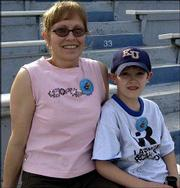 Carrie Mayhew, Lawrence, and her son Thomas, 7, watch the Kansas University Relays. They attended the event last Saturday at Memorial Stadium.
