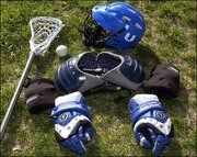 A lacrosse player's gear includes helmet, shoulder pads, elbow pads and gloves as well as a stick and ball.