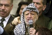 Backed by his aides, Palestinian leader Yasser Arafat gestures angrily as he speaks to supporters in front of his compound in the West Bank town of Ramallah. Arafat on Saturday brushed off new Israeli threats against him, saying that Israel would never get rid of him.