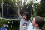 Paulina Cooper, 6, of Lawrence, shows how high she can jump on her new trampoline, which was given to her by the Make-A-Wish Foundation of Kansas. Friends and family gathered Saturday at her Lawrence home for her birthday party. Chloe Mercer, 13, holds Paulina.