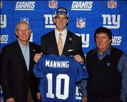 Eli Manning, center, holds up his New York Giants jersey as he poses with coach Tom Coughlin, left, and general manager Ernie Accorsi. Manning was tapped No. 1 overall in Saturday's NFL draft by the San Diego Chargers, then was traded to the Giants for their No. 4 pick, quarterback Philip Rivers, and draft picks.