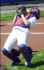 Kansas catcher Dani may, a Lawrence High product, bobbles a foul ball before making the catch for an out against Texas.