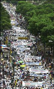 "Opposition union workers march to protest against increased unemployment in Caracas, Venezuela. The sign at bottom reads ""Mr. President, we demand jobs and security, no more deaths."" The protest was among many that took place around the world on May Day."