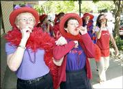 Red Hatters Alice Leitch, left, and Connie Sue Patterson march down Massachusetts Street playing kazoos. Red Hat Society members from around northeast Kansas congregated Saturday at Prairie Patches, 821 Mass. Society members, who are women older than 50, wear red hats and purple clothes to their meetings.