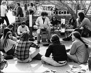 Roger Shimomura, the bespectacled man crouched to the right of the guitar player, hangs out with Kansas University students on campus. The photo was taken in 1970, one year after Shimomura joined the KU art faculty.