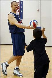 New Jersey Nets' Jason Kidd plays with his son, TJ, after practice, Saturday, May 1, 2004, in East Rutherford, N.J. as they prepare for their second round playoff series against the Detroit Pistons.