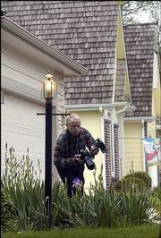 Stewart Nowlin photographs irises outside his shake-shingled home in Lawrence.