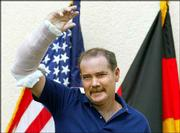 U.S. civilian contractor Thomas Hamill, from Macon, Miss., waves with his injured arm to the media from a balcony at the Regional Medical Center in Landstuhl, western Germany. Hamill is being treated in Landstuhl after escaping his Iraqi captors on Sunday. His wife, Kellie, is expected today in Germany for a reunion.