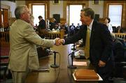 Rep. Michael O'Neal, R-Hutchinson, left, and Sen. John Vratil, R-Leawood, shake hands after reaching a compromise on the state school finance bill in conference committee at the Kansas Statehouse in Topeka. The Senate is expected to vote on Tuesday's proposal sometime today.