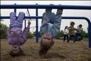 Moira Modrzynski, 6, left, and Kearston Mohney, 6, hang upside down on monkey bars at Kennedy School, 1605 Davis Road. The Lawrence children attended Kennedy's after-school program on Friday. Three Lawrence schools, including Kennedy, face the potential of seeing the federal grant money for their after-school programs run out this year.
