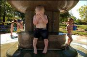 Benton Winfrey, 2, of Clinton, cools off in South Park under the fountain as other children play in the fountain. Families visited the park Wednesday and took advantage of the warm weather, with a high reaching 85. Today, however, is expected to reach 90. See page 8B for more details.