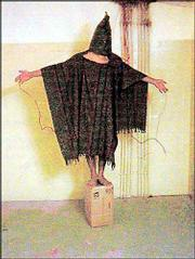 A hooded and wired Iraqi prisoner is seen at the Abu Ghraib prison near Baghdad, Iraq. U.S. soldiers allegedly told him he would be electrocuted if he fell off the box.