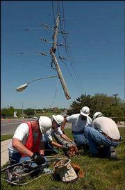 Workers from Sunflower Broadband, from left, Steve Olson, Jason Carlsten, Lorne Slan and Dave Wood work to repair a transmission line on a new pole near 23rd and Iowa streets. A semi truck caught a line and tore the pole and line down, disrupting traffic and power for several hours Thursday.