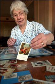 SISTER MARCELLA SCHRANT, receptionist at St. Lawrence Catholic Campus Center, displays a holy card. Her collection has about 400 cards that span 70 years.