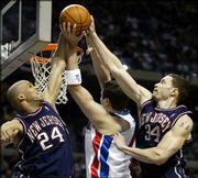 New Jersey's Richard Jefferson (24) and Aaron Williams (34) block Detroit's Mehmet Okur. The Pistons beat the Nets, 95-80, Friday in Auburn Hills, Mich.