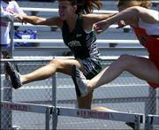 Free State's Kelsey Randall, left, competes in the 110-meter high hurdles. Randall took fourth in the event Friday in the Shawnee Mission North Relays.