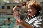 Lori Madaus, who manages the Lawrence Indoor Aquatic Center, checks the pool's chemical content. The Lawrence-Douglas County Health Department announced Friday a program aimed at keeping pools safe this summer from a repeat of last year's cryptosporidium outbreak.