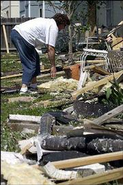 Ann Riat sifts through debris in her backyard after a tornado hit Lawrence in May 2003. Riat's home was located just north of the Aberdeen South complex and was showered with debris from the apartments.