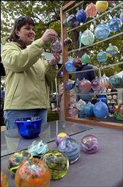 Julie Bortner-Scharf, Lawrence, looks over decorative ornaments at Art in the Park. The 43rd annual event, sponsored by the Lawrence Art Guild, was Sunday in South Park.