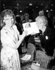 Beth Ankerholz, left, Bert Nash Community Mental Health Center information technology director, and Lauraine Mulally, Lawrence, look at a copy of the center's history. A 1940 photo of Mulally and Dr. Bert Nash appears on the page at left. The women attended the center's 18th annual Pioneer Celebration on April 20.