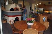 "Louis Copt builds a fire in his authentic Italian pizza oven, the focal point of the home and of the couple&squot;s frequent ""make your own pizza"" parties."