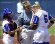 Kansas University coach Tracy Bunge, center, and catcher Dani May, left, talk to pitcher Kassie Humphreys during the fourth inning. Iowa State scored two of its three runs during the inning en route to a 3-2 victory against KU on Saturday at Arrocha Ballpark.