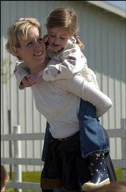 While other children ride a pony, Hannah Kate Mulanax, 5, hops on the back of her mother, Jamie Mulanax, for a hug.