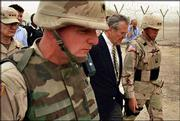 "U.S. Defense Secretary Donald Rumsfeld, center, tours the prison of Abu Ghraib with Maj. Gen. Geoffrey Miller, right, commander of the prison system in Iraq, shortly after his arrival in Baghdad. Rumsfeld said Thursday ""the abuses of a few"" would not change prison policies."