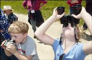 Colby Lake, 5, and his sister Chelsea, 6, of Topeka, aim their binoculars at a pair of adult eagles flying near the nest in a tree where a climber was capturing the pair's two young eagles for banding.