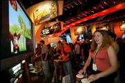 "Katie Stone, 27, far right, plays Nintendo's ""Donkey Konga"" at the Electronic Entertainment Exposition in Los Angeles. Last week's exposition was the world's leading interactive entertainment trade event."