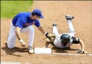 Kansas University first baseman Travis Metcalf fails to tag Missouri's Cosme Caballero in time during a pick-off play. The Jayhawks won the third and final game of the weekend series, 4-3, Sunday afternoon at Hoglund Ballpark.
